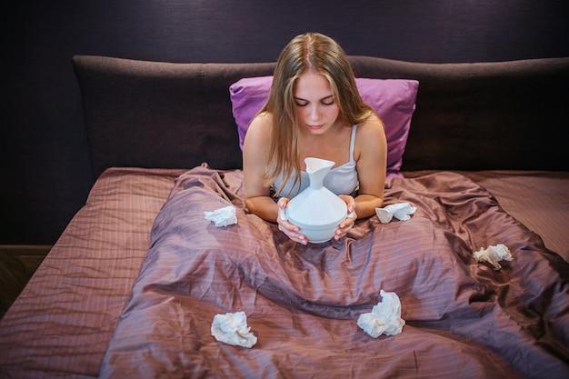 Joven rubia se sienta en la cama. ella sostiene el inhalador y lo mira con desprecio. hay muchos tejidos blancos usados en la cama. ella sufre de enfermedad.