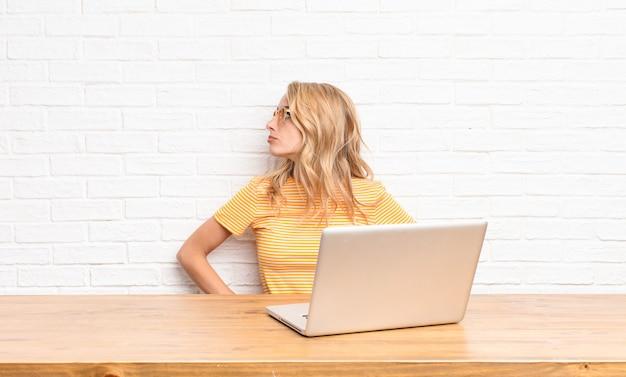 Joven rubia se siente confundida o llena o dudas y preguntas, preguntándose, con las manos en las caderas, vista trasera usando una computadora portátil