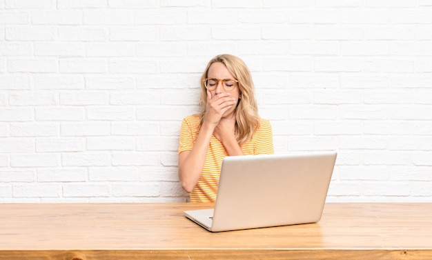 Joven rubia se siente enferma con dolor de garganta y síntomas de gripe, tos con la boca cubierta usando una computadora portátil