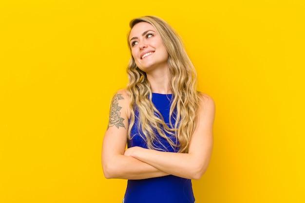 Joven rubia se siente feliz, orgullosa y esperanzada, preguntándose o pensando, mirando hacia arriba para copiar espacio con los brazos cruzados contra la pared amarilla