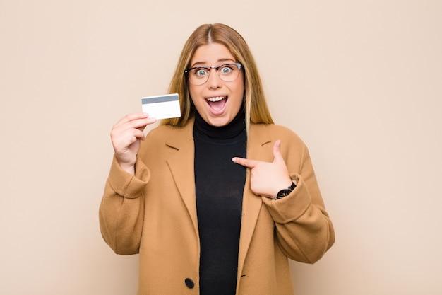 Joven rubia se siente feliz, sorprendida y orgullosa, apuntando a sí misma con una mirada emocionada y asombrada con una tarjeta de crédito
