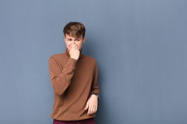 Joven rubia sintiéndose disgustado, tapándose la nariz para evitar oler un hedor desagradable y desagradable aislado contra la pared plana