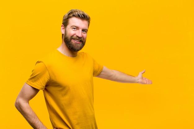 Joven rubia sintiéndose feliz y alegre, sonriendo y dándote la bienvenida, invitándote a entrar con un gesto amistoso contra la pared naranja