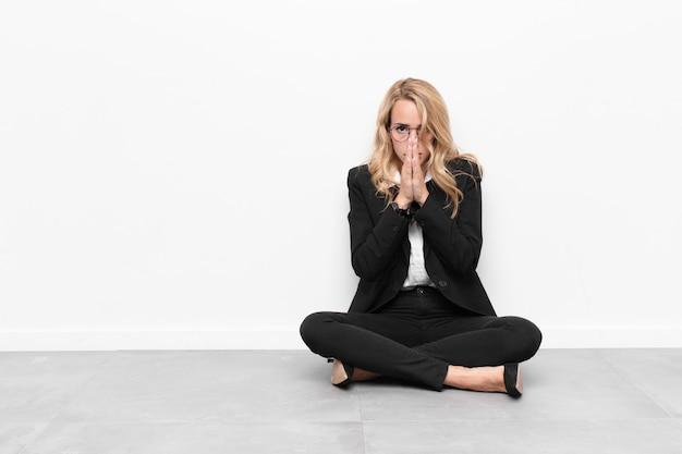 Joven rubia sintiéndose preocupada, esperanzada y religiosa, rezando fielmente con las palmas presionadas, pidiendo perdón sentada en el suelo
