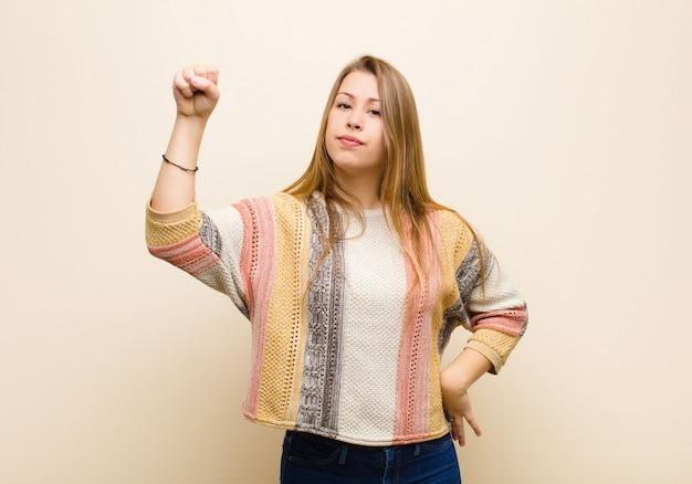 Joven rubia sintiéndose seria, fuerte y rebelde, levantando el puño, protestando o luchando por la revolución contra la pared beige