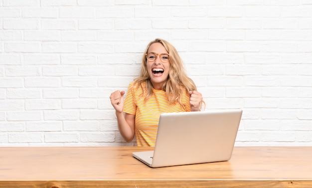 Joven rubia sintiéndose sorprendida, emocionada y feliz, riendo y celebrando el éxito, diciendo ¡guau! usando una laptop
