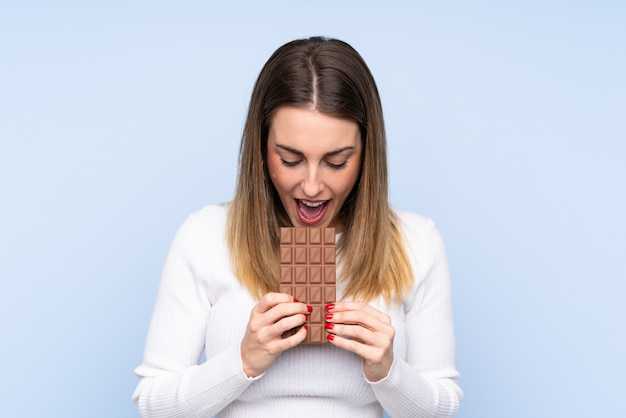 Joven rubia sobre pared aislada comiendo una tableta de chocolate