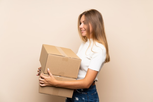 Joven rubia sobre pared aislada sosteniendo una caja para moverla a otro sitio