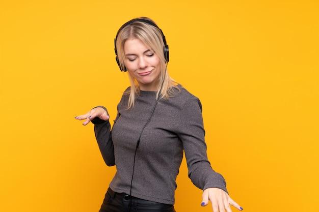 Joven rubia sobre pared amarilla aislada escuchando música y bailando