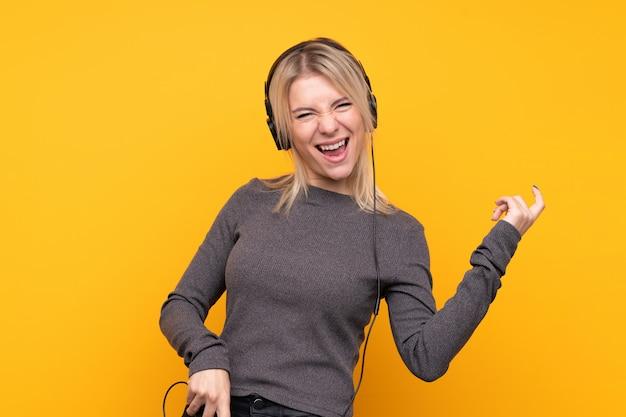 Joven rubia sobre pared amarilla aislada escuchando música y haciendo gesto de guitarra