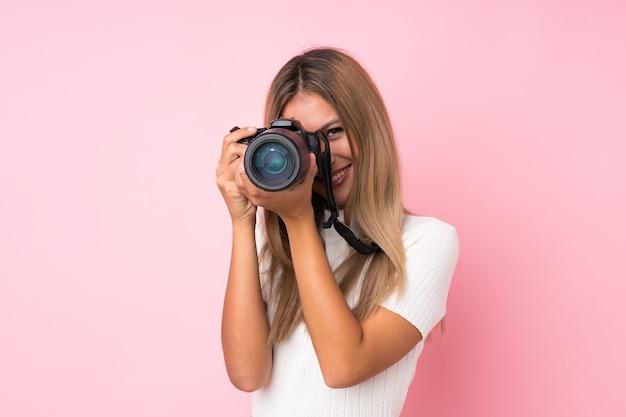 Joven rubia sobre rosa aislado con una cámara profesional