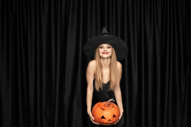 Joven rubia con sombrero negro y traje sobre fondo negro. modelo femenino atractivo y sensual. halloween, viernes negro, cyber monday, rebajas, otoño