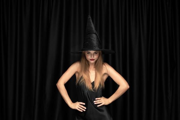 Joven rubia con sombrero negro y traje sobre fondo negro. modelo femenino caucásico atractivo y sensual. halloween, viernes negro, cyber monday, rebajas, otoño