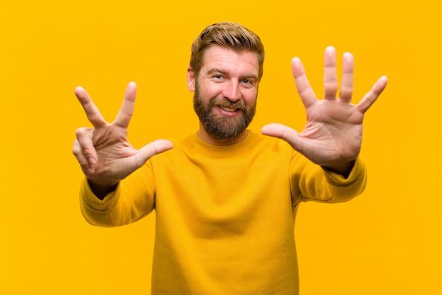 Joven rubia sonriendo y mirando amigable, mostrando el número ocho u octavo con la mano hacia adelante, contando contra la pared naranja