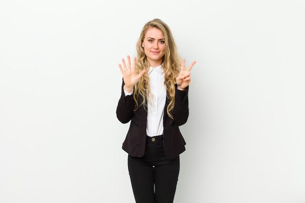 Joven rubia sonriendo y mirando amigable, mostrando el número siete o séptimo con la mano hacia adelante, contando hacia atrás en la pared blanca