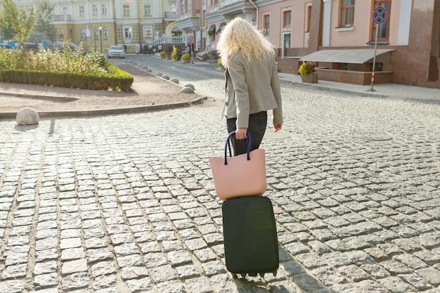 Joven rubia sonriente con bolsa de viaje