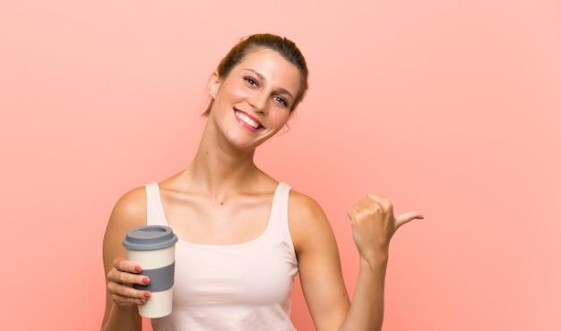 Joven rubia sosteniendo un café para llevar apuntando hacia un lado para presentar un producto