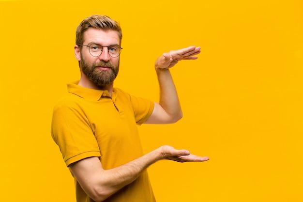 Joven rubia sosteniendo un objeto con ambas manos en el espacio de copia lateral, mostrando, ofreciendo o publicitando un objeto
