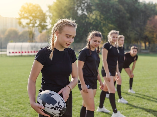 Joven rubia sosteniendo una pelota de rugby