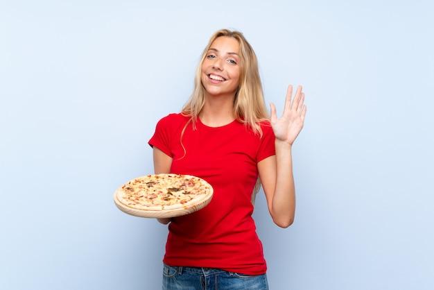 Joven rubia sosteniendo una pizza sobre pared azul aislado saludando con la mano con expresión feliz