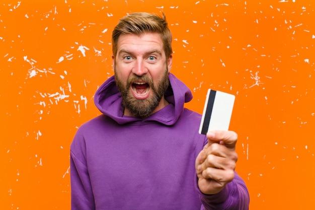 Joven rubia con una tarjeta de crédito usando una sudadera con capucha púrpura contra la pared naranja dañada