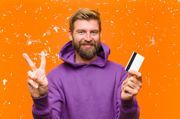 Joven rubia con una tarjeta de crédito vistiendo una sudadera con capucha púrpura contra naranja dañada
