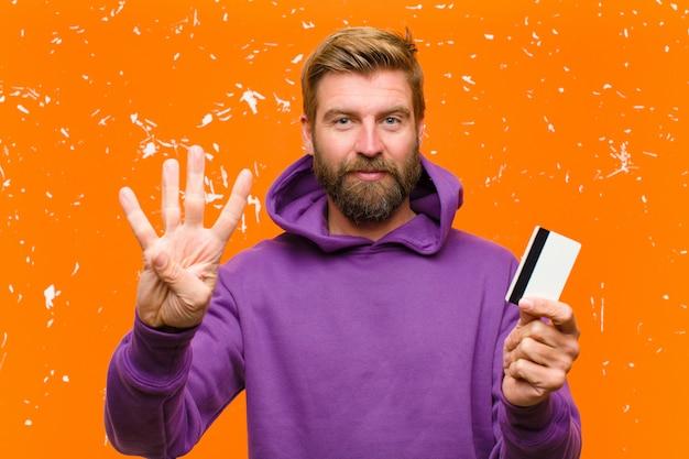 Joven rubia con una tarjeta de crédito vistiendo una sudadera con capucha púrpura contra la pared naranja dañada