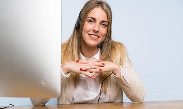 Joven rubia telemarketer mujer y sonriente