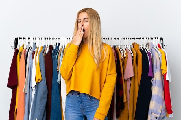 Joven rubia en una tienda de ropa bostezando y cubriendo la boca abierta con la mano