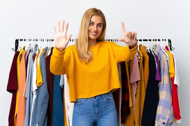 Joven rubia en una tienda de ropa contando siete con los dedos