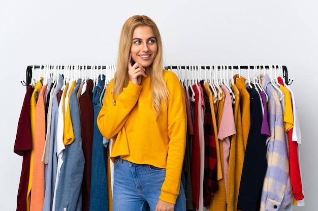Joven rubia en una tienda de ropa pensando en una idea mientras mira hacia arriba