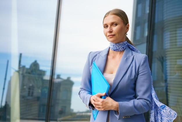 Una joven rubia con un traje formal sostiene documentos en el fondo de un edificio comercial. concepto de trabajo.