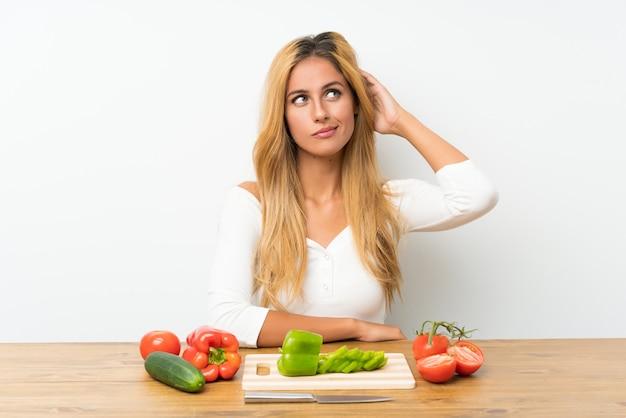 Joven rubia con verduras en una mesa con dudas y con expresión de la cara confusa