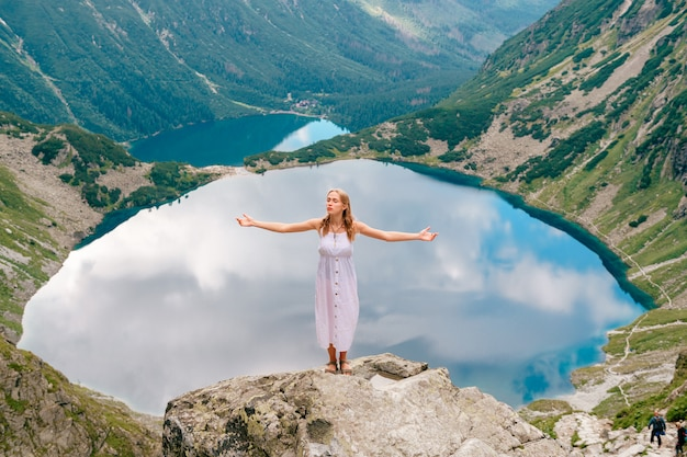 Joven rubia en vestido blanco de pie en piedra en las montañas con las manos separadas y hermoso lago detrás.