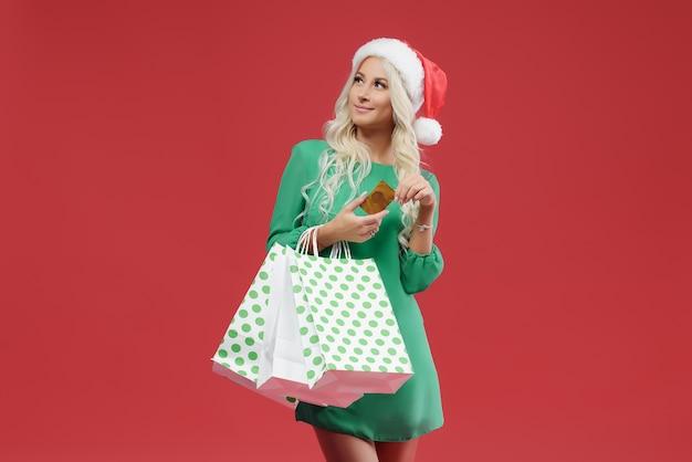 Una joven rubia con un vestido verde sostiene paquetes y una tarjeta de crédito. compras de navidad