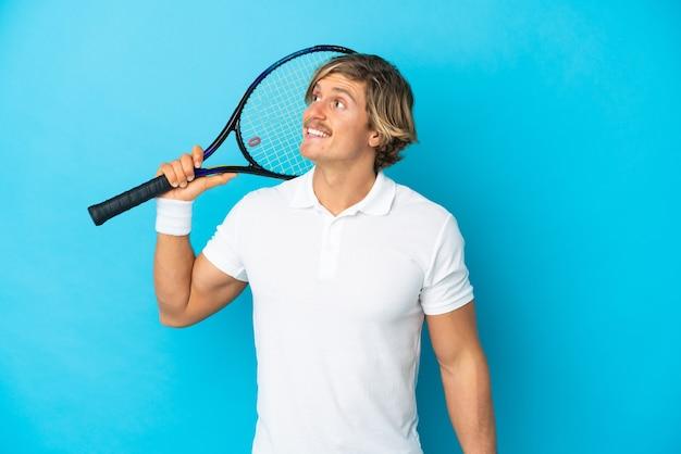 Joven rubio aislado jugando al tenis y mirando hacia arriba