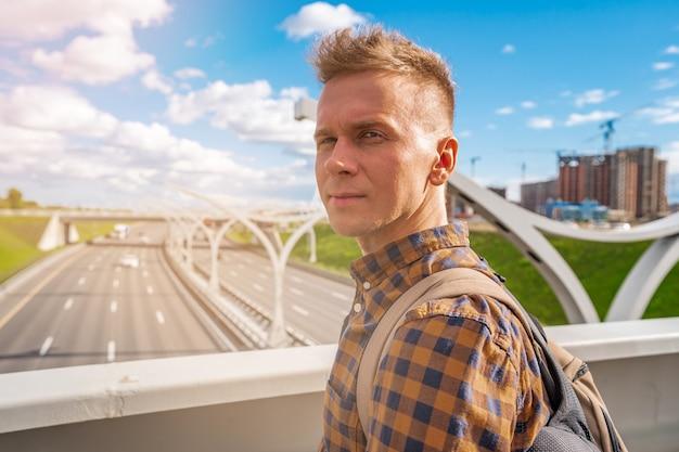 Un joven rubio en camisa mirando la sección de la carretera de diámetro de alta velocidad occidental de san petersburgo