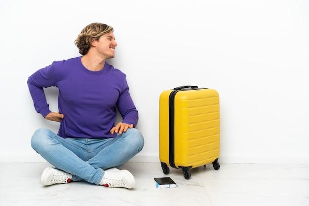 Joven rubio con maleta sentada en el suelo sufre de dolor de espalda por haber hecho un esfuerzo