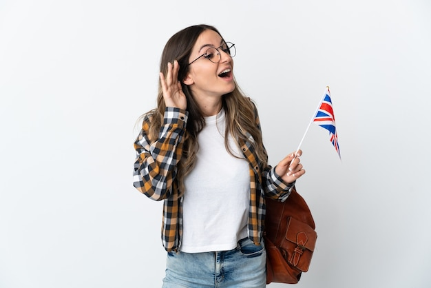 Joven rumana sosteniendo una bandera del reino unido aislada en la pared blanca escuchando algo poniendo la mano en la oreja