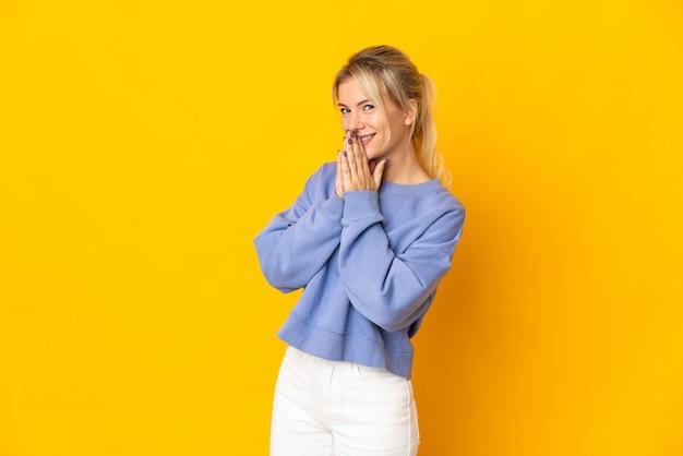 La joven rusa aislada en amarillo mantiene la palma unida. la persona pide algo