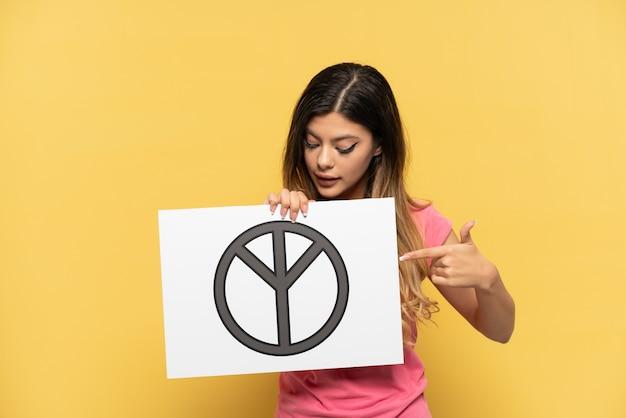 Joven rusa aislada sobre fondo amarillo sosteniendo un cartel con el símbolo de la paz y apuntándolo