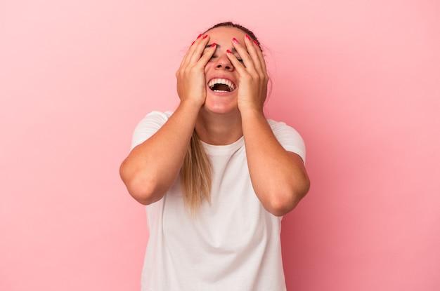 Joven rusa aislada sobre fondo rosa se ríe con alegría manteniendo las manos en la cabeza. concepto de felicidad.