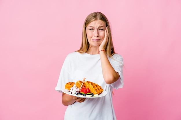 Joven rusa comiendo un gofre lloriqueando y llorando desconsoladamente.