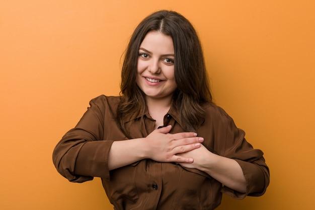 La joven rusa con curvas tiene una expresión amistosa, presionando la palma contra el pecho. concepto de amor