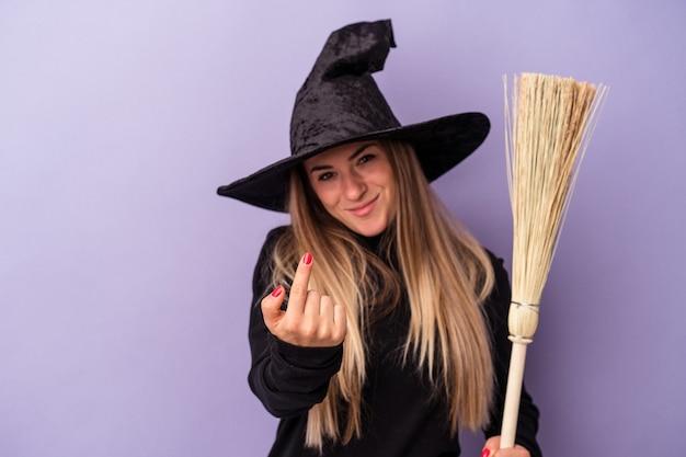 Joven rusa disfrazada de bruja sosteniendo una escoba aislada sobre fondo púrpura apuntando con el dedo como si invitara a acercarse.