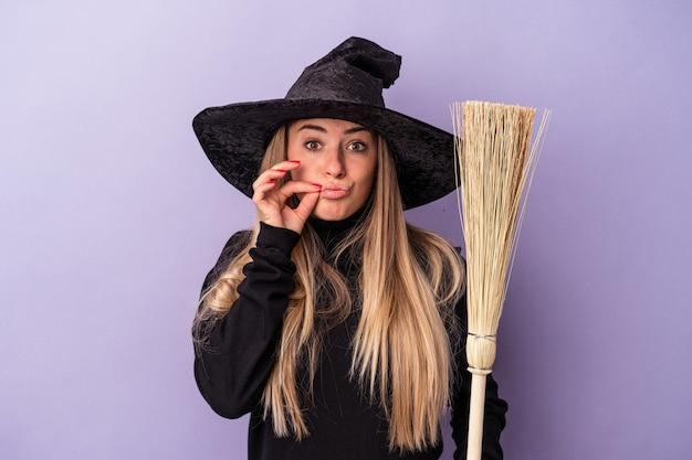 Joven rusa disfrazada de bruja sosteniendo una escoba aislada sobre fondo púrpura con los dedos en los labios guardando un secreto.