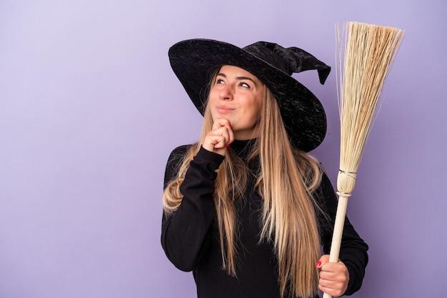Joven rusa disfrazada de bruja sosteniendo una escoba aislada sobre fondo púrpura mirando hacia los lados con expresión dudosa y escéptica.