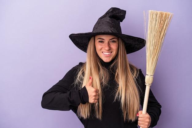 Joven rusa disfrazada de bruja sosteniendo una escoba aislada sobre fondo púrpura sonriendo y levantando el pulgar hacia arriba