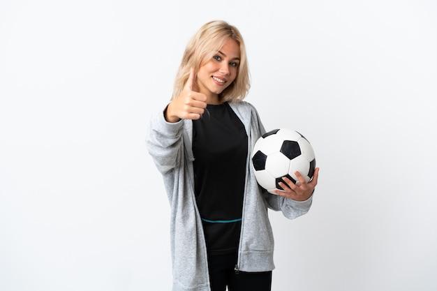 Joven rusa jugando al fútbol aislado en la pared blanca con los pulgares hacia arriba porque ha sucedido algo bueno