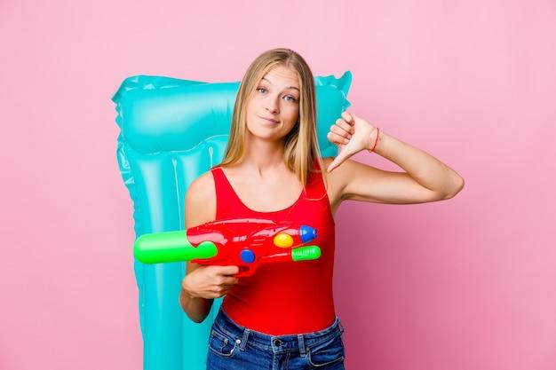 Joven rusa jugando con una pistola de agua con un colchón de aire mostrando un gesto de aversión, pulgares hacia abajo. concepto de desacuerdo